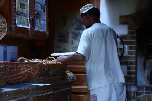 Daniel sort ses pains du four et les laisse refroidir dans de grands paniers